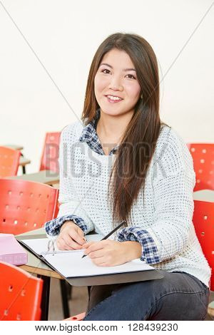 Asian girl taking notes in class in high school