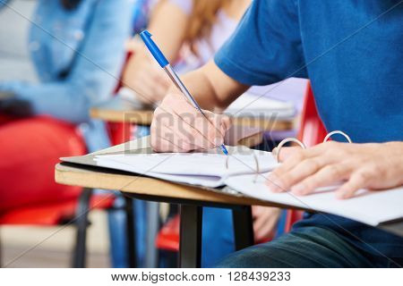Student taking notes in his notebook during a class