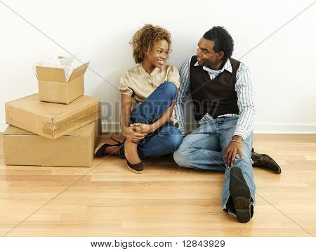 Portrait of smiling happy young couple sitting on floor of home with moving boxes.