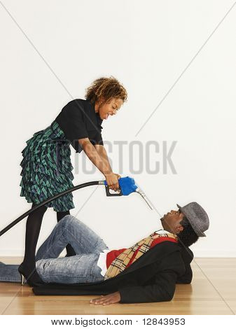 Man on floor with angry woman standing over him pointing gasoline pump nozzle at him like a gun.