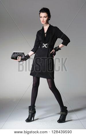 full-length fashion model in gloves holding little purse posing-light background