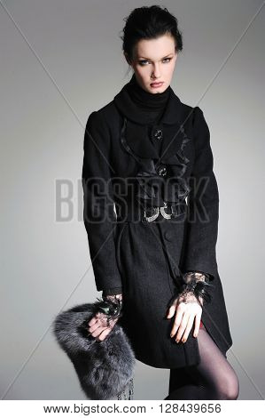 fashion model in black coat holding little purse posing on light background