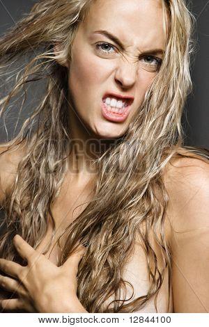 Desnudo mujer caucásica tirando de largos cabellos rubios y mirando al espectador con snarling expresión.
