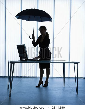 Silhouette of businesswoman standing at computer desk holding umbrella.