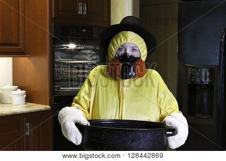 Woman in yellow HazMat suit and respirator wearing Pilgrim hat standing next to open oven in kitchen.