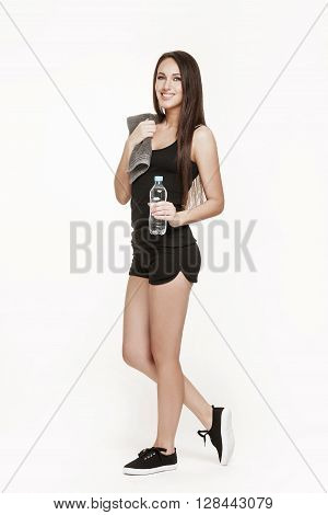 Full portrait of good looking brunette woman in sports outfit. Fit woman at the gym drinking water. Healthy lifestyle concept.