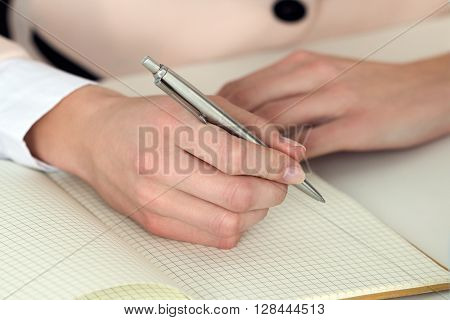 Woman hand holding silver pen ready to make note in opened notebook. Businesswoman or employee at workplace writing business ideas plans tasks at personal organizer. Office life or education concept