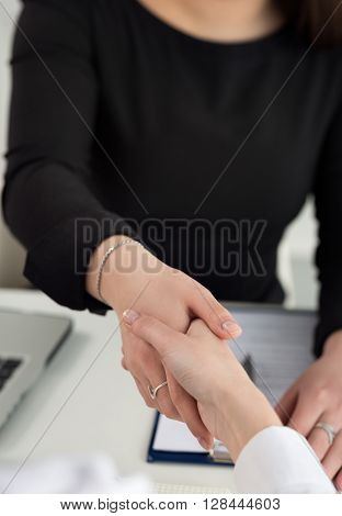 Two women handshake in office closeup. Businesswomen shaking hands. Serious business partnership and collaboration concept. Partners made deal and sealed it with handclasp. Formal greeting gesture