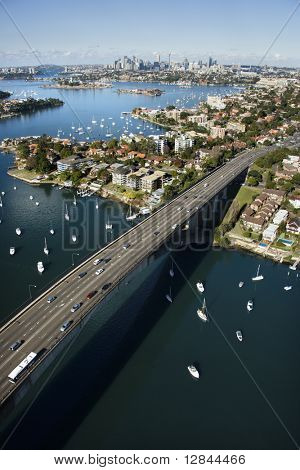 Aerial view of Victoria Road bridge and boats with distant downtown skyline in Sydney, Australia.