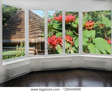 windows overlooking the branches of red ripe guelder-rose and Ukrainian old house