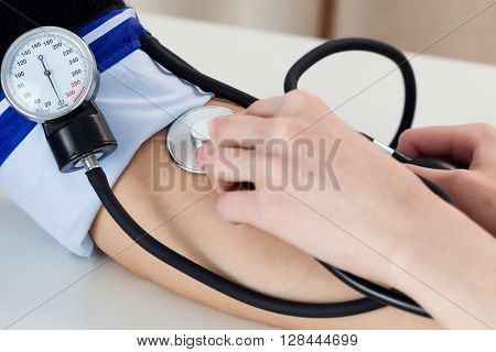 Female medicine doctor measuring blood pressure to patient. Close up view. Medical and healthcare concept