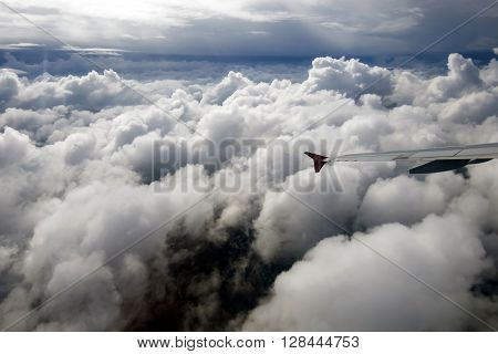 The flight of the aircraft inside the clouds. Wing view of the aircraft in motion in dense large clouds. Shooting the airplane.