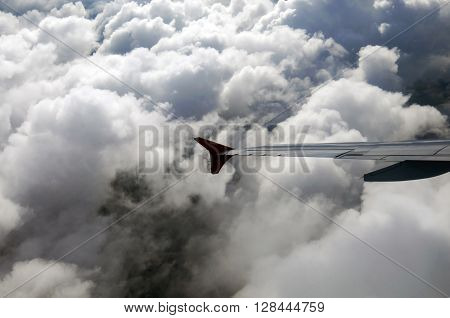 Aircraft flying inside the cloud. Wing view of the aircraft in motion in dense large clouds. Shooting the plane.