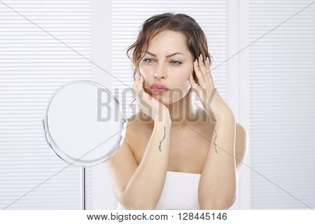 Young beautiful woman looking in mirror