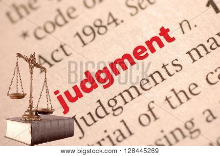 Dictionary definition of judgment and scales of justice on the book. Close-up view with paper textures