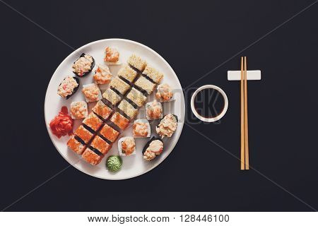 Japanese food restaurant, sushi maki gunkan roll plate or platter set. Chopsticks, ginger and wasabi. Sushi at white round plate, black background. Top view with soy sauce
