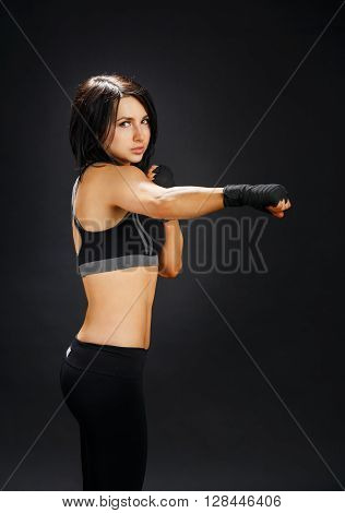 Young sportive woman shows good fitness shape. Sporty strong body, girl in fitness wear shows fist, tae bo fitness. Slim brunette at black background, studio portrait. Female fighter.