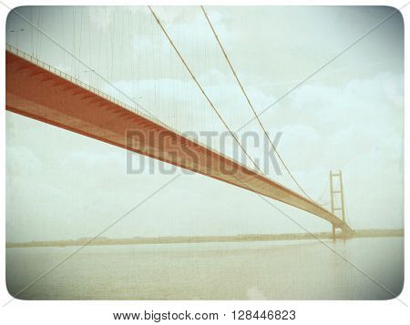 Faded old film effect applied to image suspension bridge over the River Humber