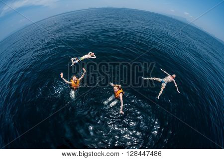 Group of friends swimming and relaxing in the open sea