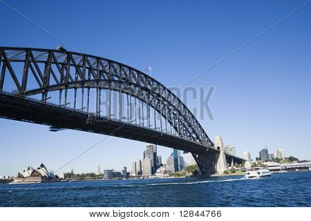 Sydney Harbour Bridge with view of downtown buildings and Sydney Opera House in Australia.