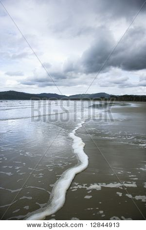 Ocean with distant mountains and cloudy sky in Daintree Rainforest, Australia.