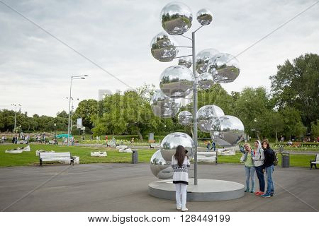 MOSCOW, RUSSIA - JUN 29, 2015: People walk in Gorky park near tree made of metal rod and mirror inflatable balls. The total area of the park is 219.7 hectares.
