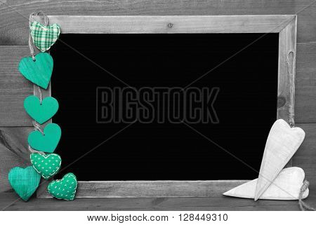 Chalkboard With Copy Space For Advertisement. Many Green Hearts. Wooden Background With Vintage, Rustic Or Retro Style. Black And White Image With Colored Hot Spots.