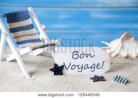 Summer Label With French Text Bon Voyage Means Good Trip. Blue Wooden Background. Card With Holiday Greetings. Beach Vacation Symbolized By Sand, Deck Chair And Shell.