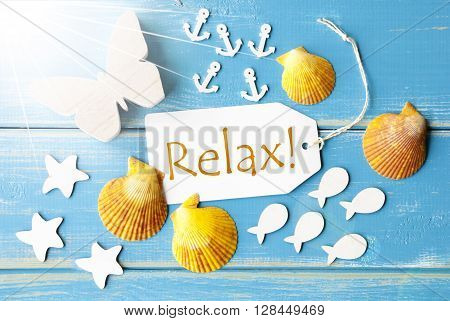 Flat Lay View Of Label With English Text Relax. Sunny Summer Greeting Card. Butterfly, Shells And Fishes On Blue Wooden Background