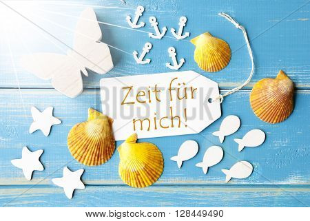 Flat Lay View Of Label With German Text Zeit Fuer Mich Means Time For Me. Sunny Summer Greeting Card. Butterfly, Shells And Fishes On Blue Wooden Background