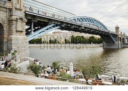 MOSCOW, RUSSIA - JUN 29, 2015: People in outdoor cafe at the support of Pushkinsky (Andreevsky) bridge over Moscow river. Bridge connects Pushkin embankment Neskuchnyi Garden with Frunze Embankment.