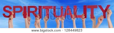 Many Caucasian People And Hands Holding Red Straight Letters Or Characters Building The English Word Spirituality On Blue Sky