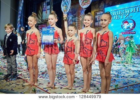 RUSSIA, KRASNOGORSK - DEC 12, 2014: Group of girls gymnasts Box of Pencils stands on stage in House of Moscow Oblast Government with diploma and cup of Moscow open all-russia festival Star Children.