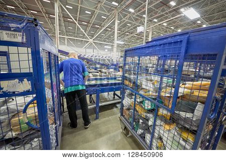 RUSSIA, MOSCOW - DEC 16, 2014: Worker of automated sorting center in Vnukovo at conveyor. Moscow Automated sorting center - the largest in Eastern Europe.