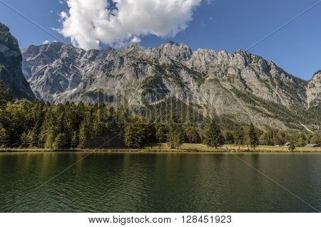 view over koenigssee to Watzmann from sun illuminated mountain massif impressive white cloudscape over the mountain chain with bright blue sky shore line with trees