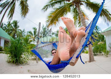 Happy couple on tropical vacation relaxing in hammock