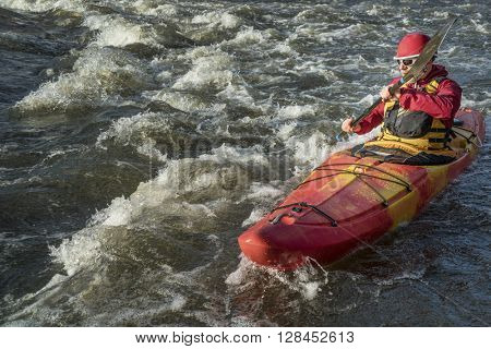 senior whitewater kayaker paddling upstream the river rapid