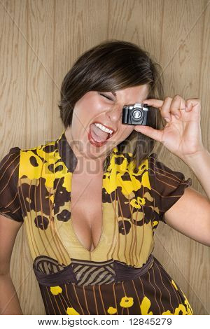 Caucasian mid adult brunette woman looking through miniature toy camera and making facial expression.