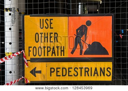 A sign for pedestrians to Use Other Footpath in yellow and orange color attached to metal net fence.