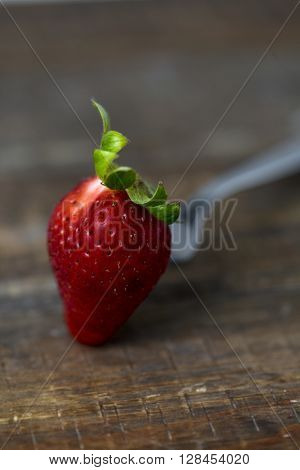 closeup of a ripe strawberry in a fork on a rustic wooden table