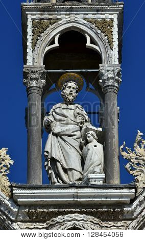 Medieval statue of Matthew the Apostle with small angel from Saint Mark basilica monumental facade in Venice