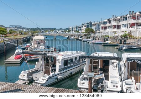 KNYSNA SOUTH AFRICA - MARCH 3 2016: The marina at the historic Thesens Island with luxury homes. Several types of boats including houseboats are visible