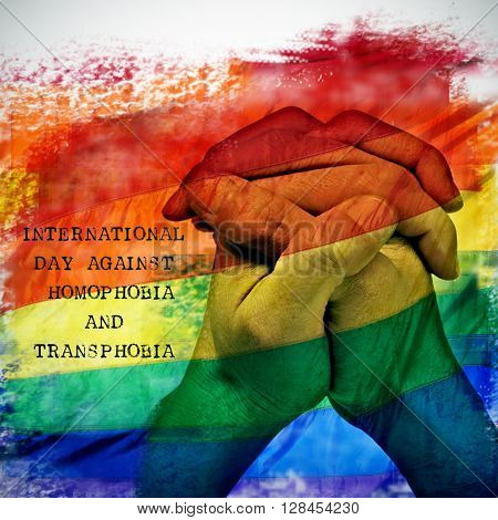 double exposure of a rainbow flag and the hands of a young man put together, and the text international day against homophobia and transphobia
