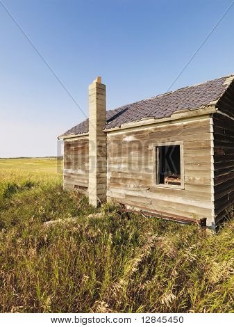 Abandoned wooden house in state of disrepair in rural countryside.