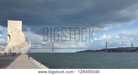 LISBON, PORTUGAL - OCTOBER 20: Monument to the Discoveries along the Tagus River with 25 de Abril Bridge and stormy weather OCTOBER 20, 2015 in Lisbon, Portugal