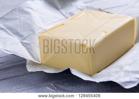 whole block butter in open packaging on white wooden background front view