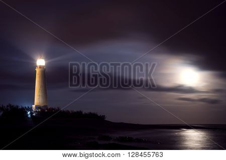 Lighthouse on coast at night with moonlight in the sky beach environment landscape.