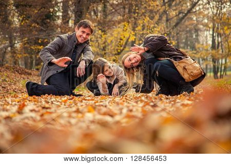 Family of three stand in park on an autumn day.