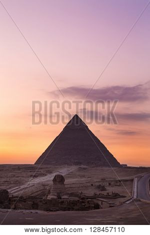 The Sphinx at sunset with great pyramid of Giza in background.