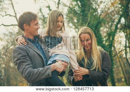 Playful family of three walk in a park on an autumn day.
